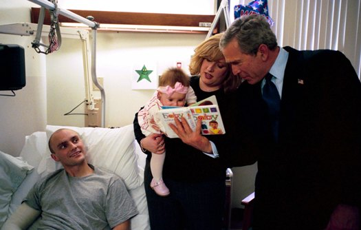 President George W. Bush reads a baby book with U.S. Army Reservist First Lieutenant Brandan Mueller of Webster Groves, Mo., his wife Amanda, and their daughter Abigail