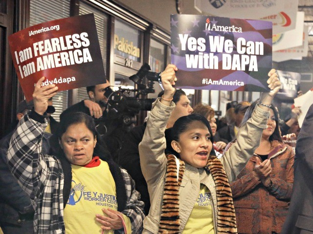 illegal women with DACA and DAPA signs