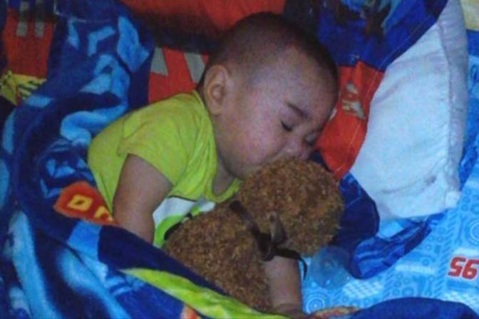 Isaiah Perez Pequeno and his Teddy Bear which contains his dead twin's ashes within